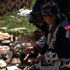 Image of an Ainu woman sitting on a mat outdoors