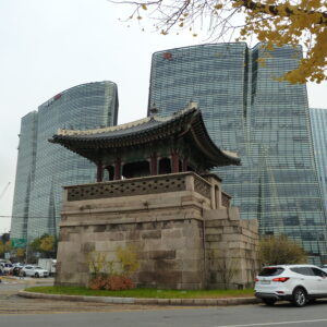 An image of an old watchtower in front of skyscrapers in Seoul, Korea.