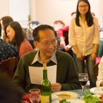 Man smiling at another person off camera at a restaurant gathering