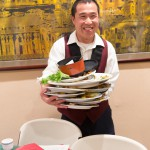 Waiter holding a mountain of dishes